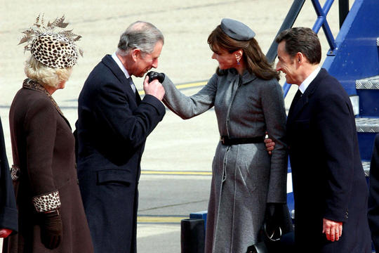 Prince Charles buckles some swash as he busses the hand of French First Lady Carla Bruni upon her arrival in Britain on March 28. [Source: thelondonpaper]