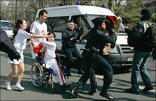 Police officers apprehend a pro-Tibet demonstrator waving a Tibetan flag (right) as he tries to interrupt the Olympic torch parade while Chinese athlete Jin Jing (left, in wheelchair) guards the torch April 7, 2008, near the Eiffel tower in Paris. [Photo by Thibault Camus/AP/NPR]