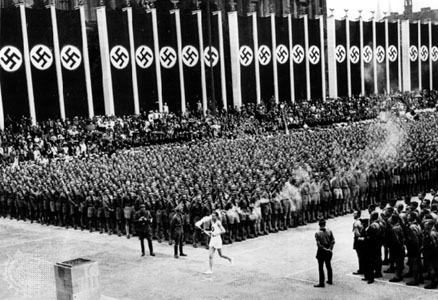 A German runner carries the Olympic flame into Berlin's swastika-draped stadium in 1936. [Source: Wikipedia]
