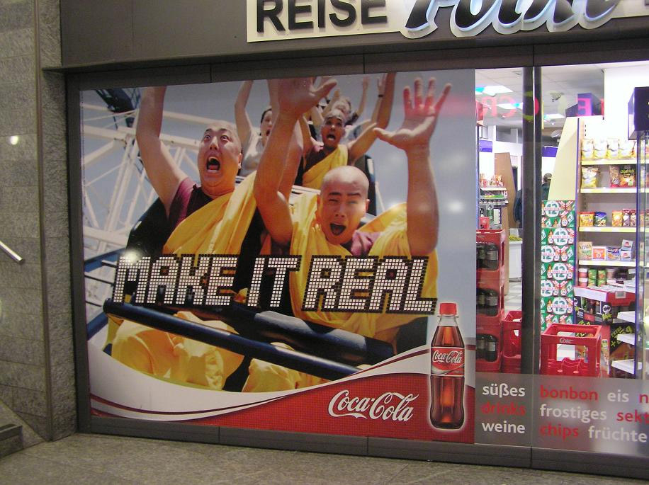 "A Coca-cola ad on the Berlin subway features exultant Tibetan monks on a roller coaster with the Coke slogan, ""Make It Real."""