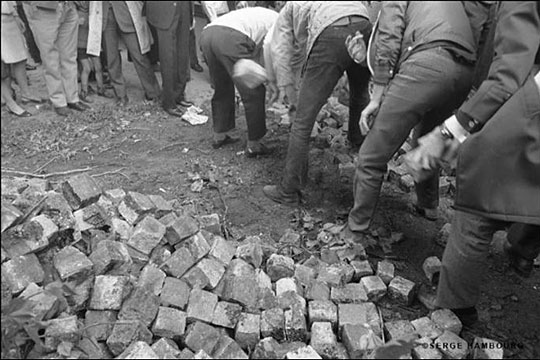 """Students dig up cobblestones to throw at police. The layer of sand below the stones led to the slogan, """"Under the cobblestones, the beach."""" [Photo by Serge Hambourg/via NPR]"""