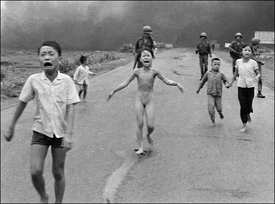 Nine0year-old Kim Phuc and other children run down a road in Vietnam after a napalm attack. The iconic photo won a Pulitzer Prize for photographer Nick Ut. [Source: AP/NPR]
