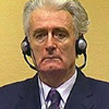 Radovan Karadzic listens to a translation of charges levied against him at the War Crimes Tribunal in The Hague. [Source: PRI's The World]