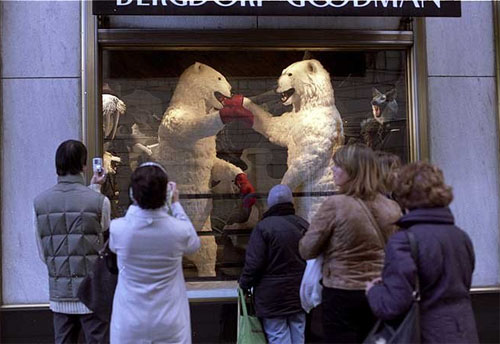 Sidewalk shoppers on Fifth Avenue in New York marvel at boxing polar bears in a department store window display.  [Photo by Bill Cunningham/NYT]