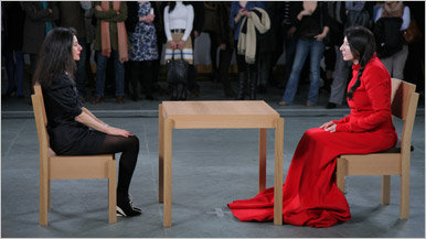 Photo shows installation view of Marina Abramovic's performance The Artist Is Present at The Museum of Modern Art, 2010. Photo by Scott Rudd. For her longest solo piece to date, Abramovic will sit in silence at a table in the Museum's Donald B. and Catherine C. Marron Atrium during public hours, passively inviting visitors to take the seat across from her for as long as they choose within the timeframe of the Museum's hours of operation. Although she will not respond, participation by Museum visitors completes the piece and allows them to have a personal experience with the artist and the artwork. © 2010 Marina Abramovic. Courtesy the artist and Sean Kelly