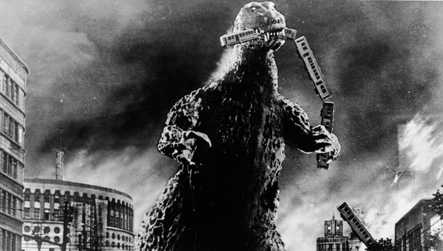 Radioactive monster Godzilla stomps through a city and eats a commuter train in a scene from Godzilla, King of the Monsters!, directed by Ishiro Honda and Terry O. Morse. The 1956 film was a re-edited version of the 1954 Japanese film Gojira, directed by Honda. [Source: Embassy Pictures/Getty Images/NPR]
