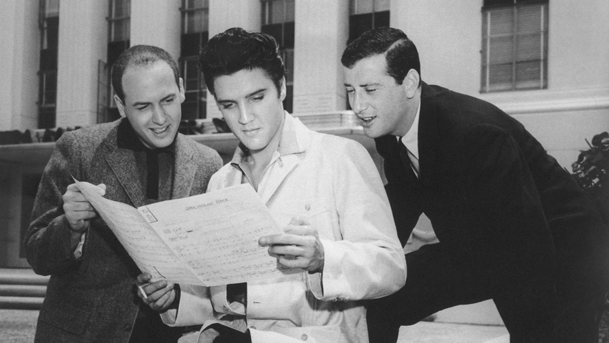 "Jerry Leiber (right) looks over Elvis Presley's shoulder at the sheet music for ""Jailhouse Rock"" in Los Angeles in 1957. His songwriting partner Mike Stoller stands to the left. Stoller played the piano in the film. [Source: Michael Ochs Archives/Getty Images/NPR]"