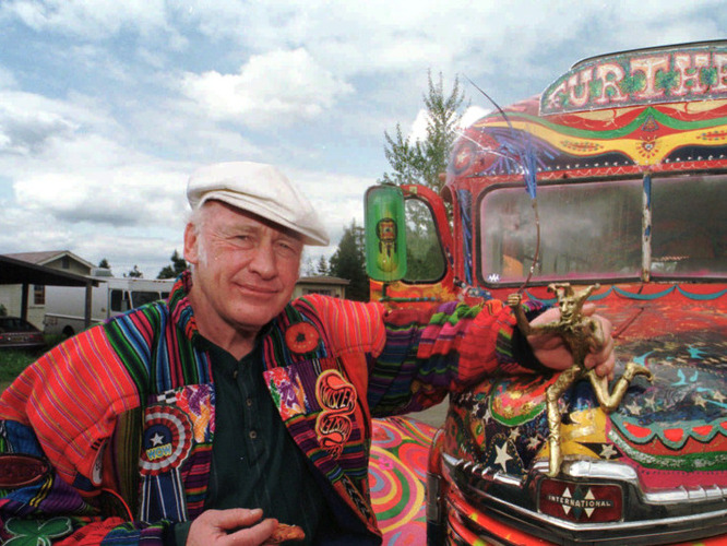 "Author Ken Kesey poses in 1997 with his bus, ""Further,"" a descendant of the vehicle that carried Kesey and the Merry Pranksters on the 1964 trip immortalized in Tom Wolfe's book The Electric Kool-Aid Acid Test. Kesey, who died in 2001, is the subject of the new documentary Magic Trip. [Source: Jeff Barnard/AP/NPR]"